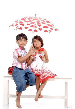 indian boy: twin brother and sister covering each other in umbrella  Stock Photo