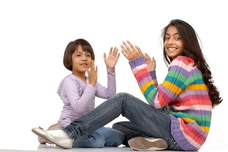 two indian girls sitting and playing clapping hands