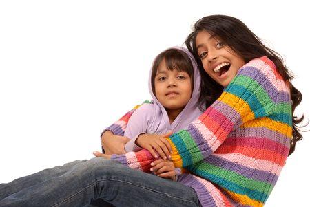 portrait of elder sister holding little sister on white background  Banco de Imagens