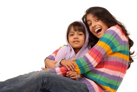 indian teenager: portrait of elder sister holding little sister on white background  Stock Photo
