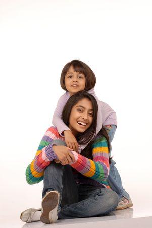 familia abrazo: dos hermanas abrazando sobre fondo blanco  Foto de archivo
