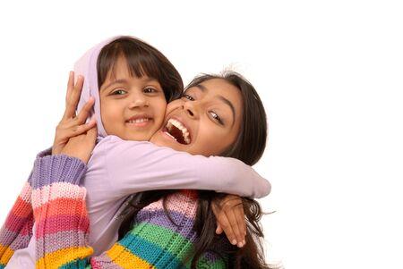 portrait of elder sister holding little sister on white background