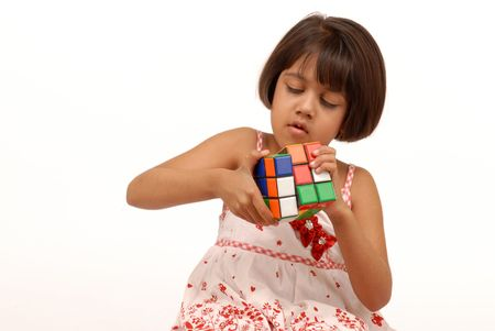 indian little girl trying hard to solve puzzle
