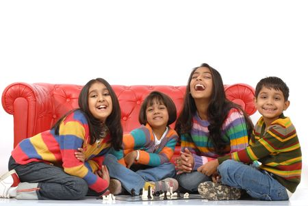 indian happy family: indian children playing board game at home