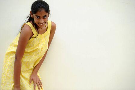 subcontinent: indian beautiful girl posing at outdoor yellow wall