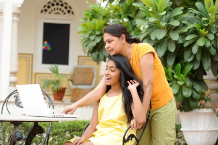 Mother and daughter working on laptop in outdoors photo