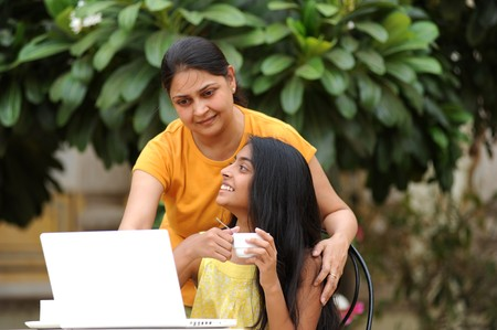 Mother and daughter working on laptop in outdoors