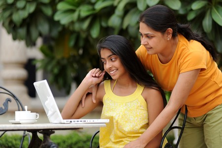 parents love: Mother and daughter working on laptop in outdoors