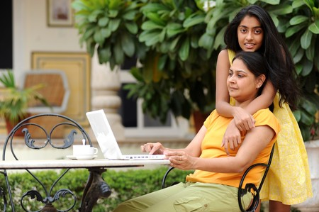 traditionally indian: Mother and daughter working on laptop in outdoors