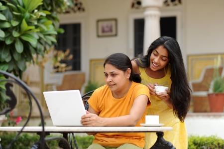 madre trabajadora: Madre e hija trabajando en la computadora port�til en el exterior Foto de archivo