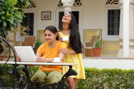 traditionally indian: working Mother and daughter enjoying house garden Stock Photo