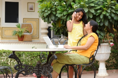 Mother working on computer with daughter in house garden photo