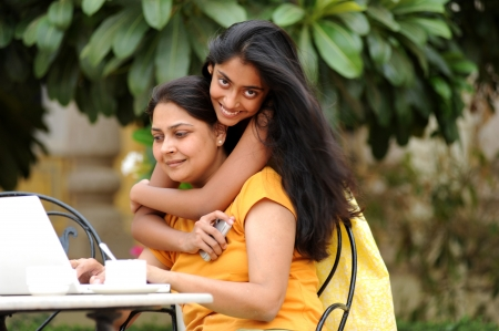Mother working on computer with daughter in house garden Standard-Bild