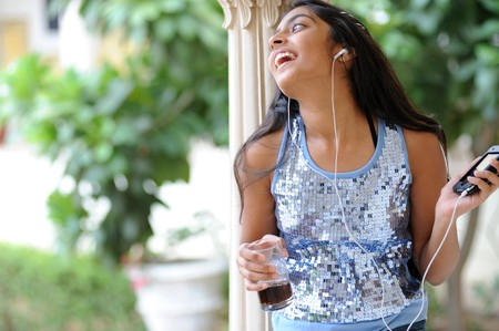 traditionally indian: beautiful young girl listening music outdoors