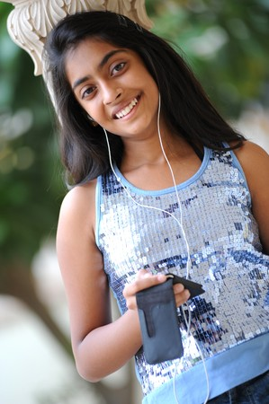 early teens: beautiful young girl listening music outdoors
