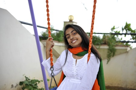 traditionally indian: indian girl expressing freedom swings outdoors