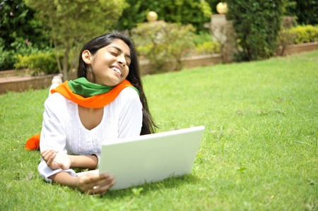 indian girl expressing freedom working on laptop photo