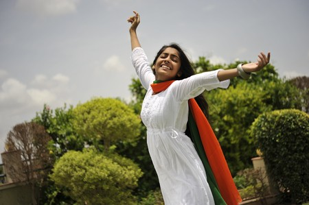 traditionally indian: indian girl expressing freedom wearing tri color