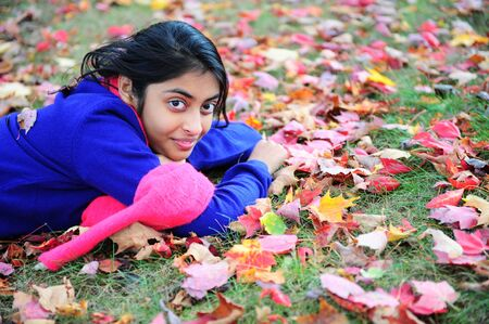 indian youth: Portrait of an autumn girl lying over leaves and smiling Stock Photo