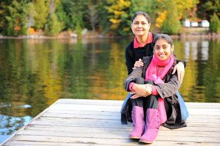 traditionally indian: Potrait of loving mother and daughter in front of lake