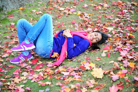 emotional freedom: autumn girl lying over leaves and smiling Stock Photo