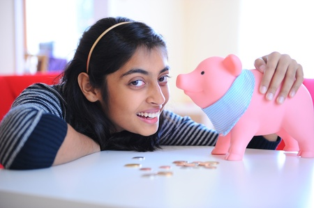 Beautiful Indian girl sitting with piggybank and coins in home photo