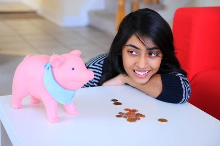 Happy young Indian girl looking to her piggybank and coins photo