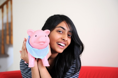 Cheerful Indian Girl holding her Piggybank with her savings photo