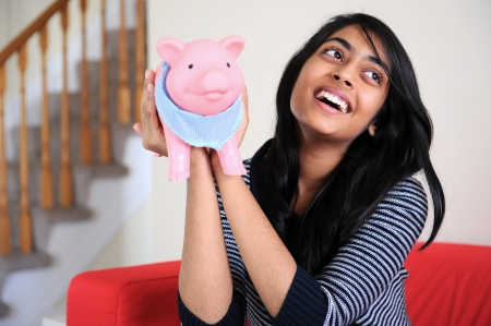 Excited Indian girl holding her piggybank in home photo