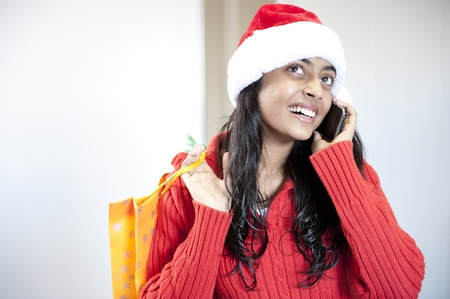 Christmas girl talking on mobile phone with shopping bag photo