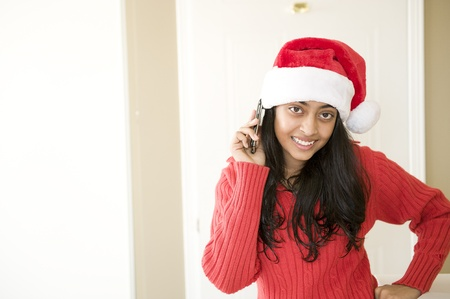 Pretty Indian girl wearing Christmas cap using mobile phone photo