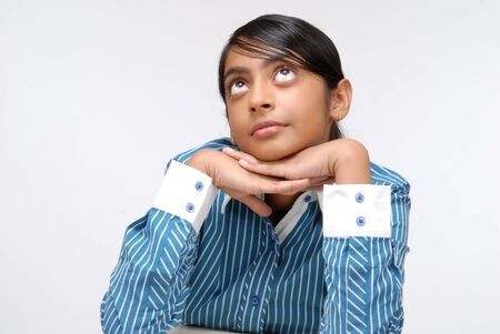 indian style sitting: A young school girl sitting at the desk, her chin resting on her hands Stock Photo