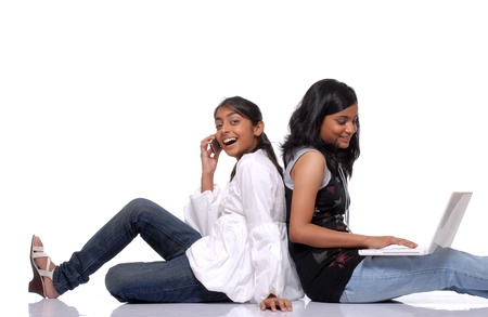 Two teenage girls use lapto and mobile phone  photo
