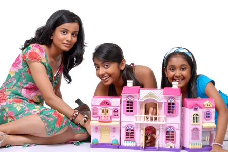 Group of three girls playing with doll house Standard-Bild