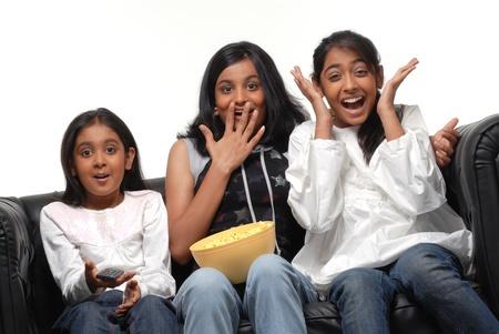 viendo television: Tres muchachas bonitas viendo la televisión en casa