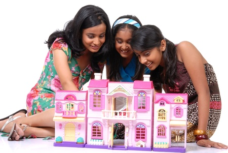 doll house: Group of three girls looking into doll house  Stock Photo