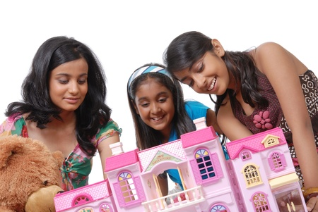 dollhouse: Group of three girls looking into doll house  Stock Photo
