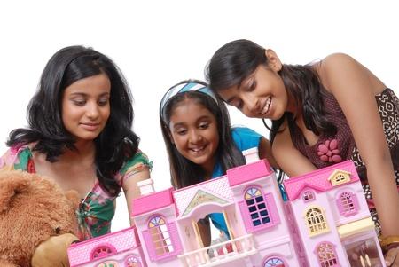 puppenhaus: Gruppe von drei M�dchen schaut in Puppenhaus