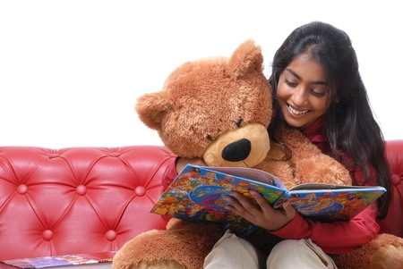toy story: Charming girl reading book with her teddy bear on Red Sofa