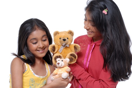 Two sisters playing with Teddy Bear in house  photo