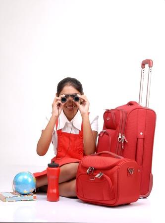 descubridor: Viajero niña sentada con la maleta y el globo buscando en binocular
