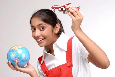 Indiase meisje houdt wereldbol en een stuk speelgoed vliegtuig plan om wereld te reizen