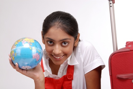 Indian girl holding a globe sitting with suitcase  photo