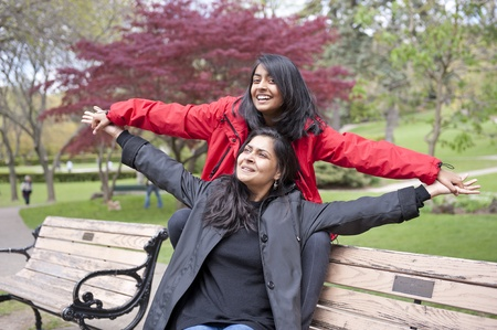 Cheerful mother and daughter enjoying in outdoors photo