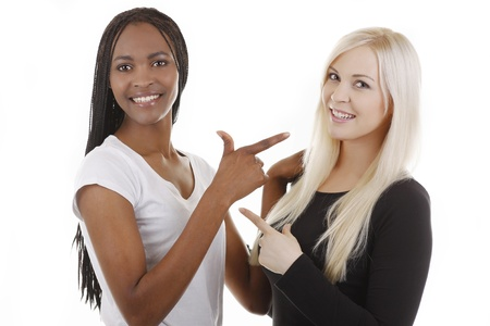 African and caucasian woman point to each other