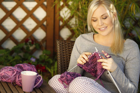Woman knitting on the terrace Imagens