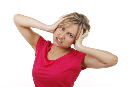 anguished: Woman closes her ears with her hands