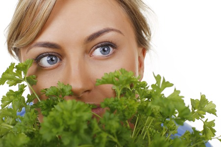face close up: Womans face close up between parsley leaves Stock Photo
