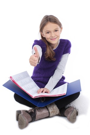 teaching material: schoolgirl with teaching material holds thumb up