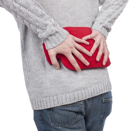 instability: man with hot bottle and back pain Stock Photo